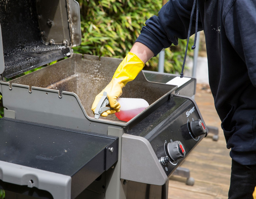 Cleaner spraying BBQ grill