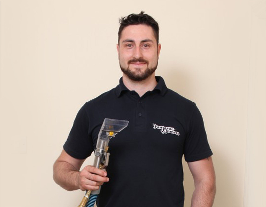 Upholstery professional holding a vaccuum cleaner
