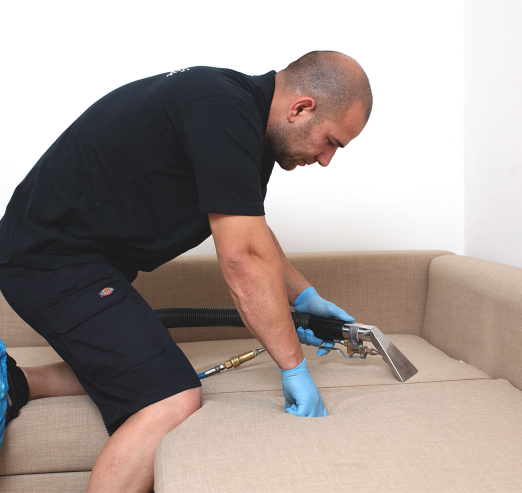 cleaner cleaning a sofa