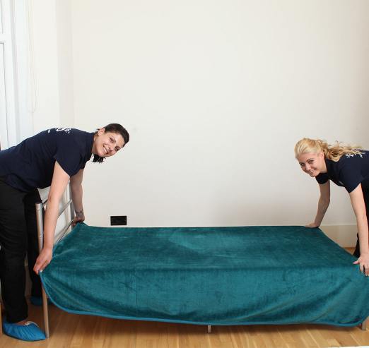 cleaners changing bed linen